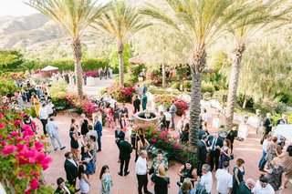 guests-and-family-at-wedding-cocktail-hour-reception-terracotta-tile-pink-bougainvillea-palm-trees
