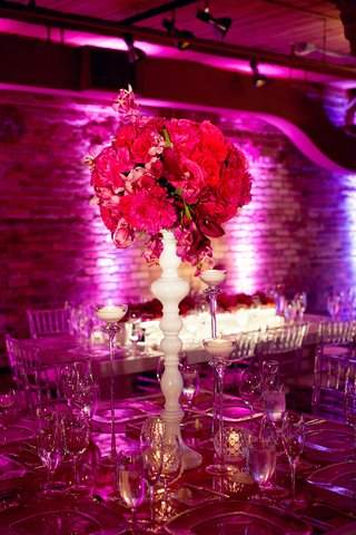 tabletop-with-pink-flowers-on-white-stand-surrounded-by-tall-thin-glass-candleholders