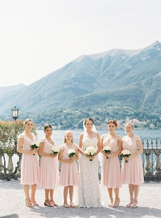 bride-in-pretty-wedding-dress-with-flower-girl-and-bridesmaids-in-short-knee-length-pink-dresses