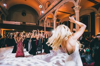 bride-tossing-bridal-bouquet-to-bridesmaids-and-girlfriends-on-dance-floor-light-vibiana