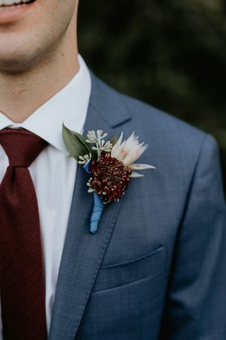 wedding-attire-groom-boutonniere-blue-ribbon-burgundy-flower-blush-flower-greenery-suit-burgundy-tie