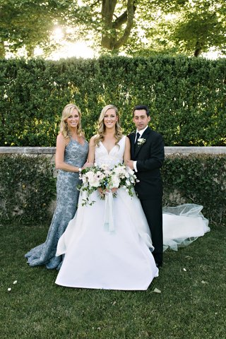 bride-in-v-neck-angel-sanchez-wedding-dress-holding-bouquet-with-father-of-bride-in-suit-and-mother