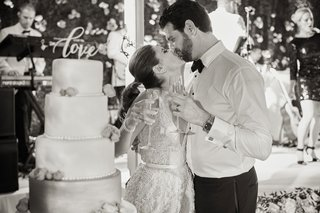 black-and-white-photo-of-bride-and-groom-with-champagne-kissing-after-cake-cutting-laser-cut-topper