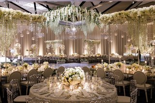 wedding-reception-ballroom-with-winter-wonderland-theme-white-flowers-greenery-silver-chairs-mirror