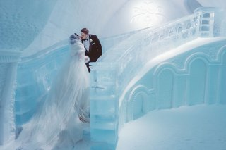 bride-in-sparkle-wedding-dress-and-cape-with-fur-headpiece-kiss-groom-ice-staircase-quebec-city