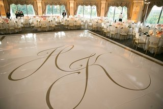 wedding-reception-with-large-white-dance-floor-gold-border-gold-monogram-with-tables-around-oheka
