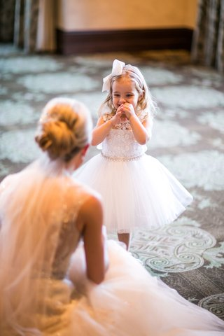 flower-girl-is-excited-to-see-bride-as-bride-kneels-in-monique-lhuillier-dress-updo
