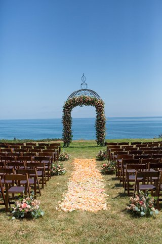 wedding-ceremony-on-grass-lawn-overlooking-pacific-ocean-flower-petal-aisle-wood-chairs-small-flower