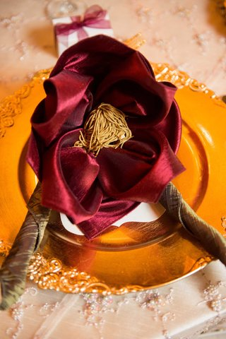 gold-charger-plate-red-napkin-interesting-configuration-orange-tassel-jewish-wedding-reception