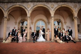 bride-and-groom-with-groomsmen-in-tuxedos-bridesmaids-in-gold-posed-at-museum-cloisters