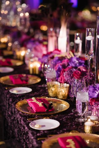 wedding-reception-table-long-purple-linens-fuchsia-pink-flowers-and-napkins-gold-candles-floating