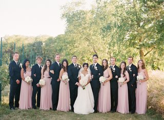 bride-and-groom-with-groomsmen-in-black-suits-and-ties-and-bridesmaids-in-pink-dresses-in-an-orchard