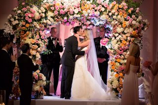 bride-in-strapless-vera-wang-wedding-dress-kissing-groom-under-flower-chuppah-at-jewish-wedding