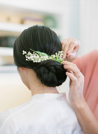 bride-with-low-chignon-hairstyle-low-bun-wedding-day-with-small-lily-of-the-valley-blooms-headpiece