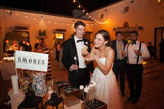 bride-and-groom-eat-from-the-smores-bar-at-their-wedding