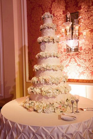 seven-tier-traditional-wedding-cake-with-flowers-between-each-tier-and-monogram-in-center