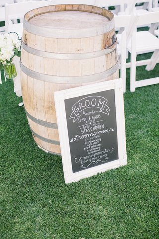 outdoor-wedding-ceremony-with-a-chalkboard-program-in-front-of-a-wine-barrel