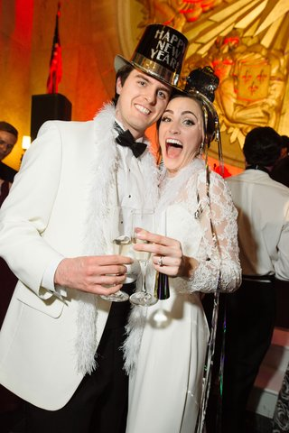 wedding-on-new-years-eve-bride-and-groom-in-white-with-feather-boa-champagne-and-new-year-top-hat