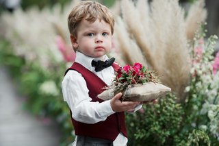 ring-bearer-in-bow-tie-and-burgundy-vest-burlap-pillow-with-pink-flowers-on-top