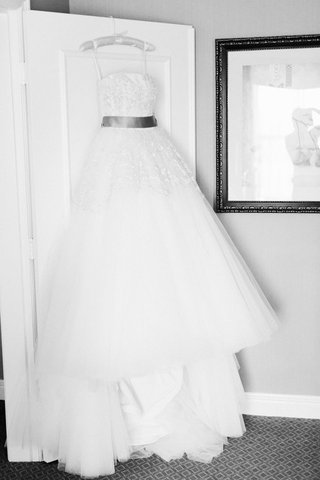 strapless-ball-gown-with-tulle-skirt-hanging-on-door