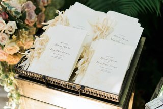 ceremony-programs-with-champagne-ribbons-on-side-and-elegant-script-in-metal-tray