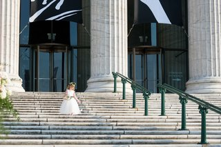 flower-girl-in-white-dress-and-flower-crown-walking-down-steps-of-the-field-museum-chicago-wedding