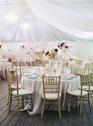 round-wedding-table-with-gold-chairs-light-blue-napkins-and-pastel-tall-flower-arrangements