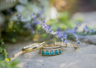 unique-gold-ring-bands-with-small-diamonds-and-turquoise-gems-on-a-rock-outdoors