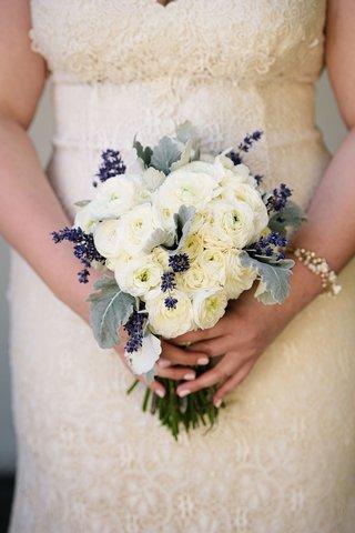 bride-in-lace-wedding-dress-holding-bouquet-with-dusty-miller-lambs-ear-ranunculus-flowers-purple