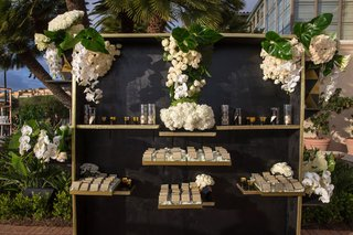 wedding-reception-outdoor-cocktail-hour-black-gold-escort-card-display-seating-assignments