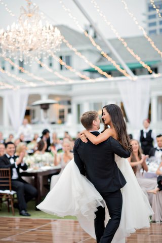 groom-lifts-bride-in-the-air-during-first-dance-bride-in-reem-acra-wedding-dress-with-her-hair-down