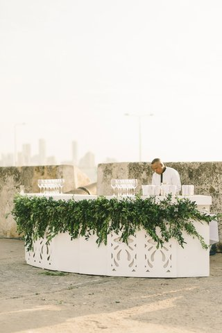 outdoor-bar-for-champagne-and-wine-at-ceremony-laser-cut-cutouts-greenery-bartender-skyline