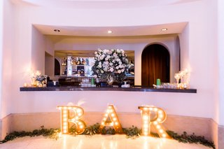 wedding-reception-after-party-dancing-ballroom-flowers-on-bar-with-eucalyptus-bar-letter-sign
