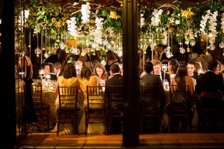 wedding-reception-view-of-guests-at-long-tables-from-outside-of-venue-space-high-centerpieces