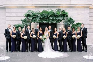wedding-party-bride-groom-bridesmaids-and-groomsmen-in-front-of-ceremony-arch-tropical-greenery