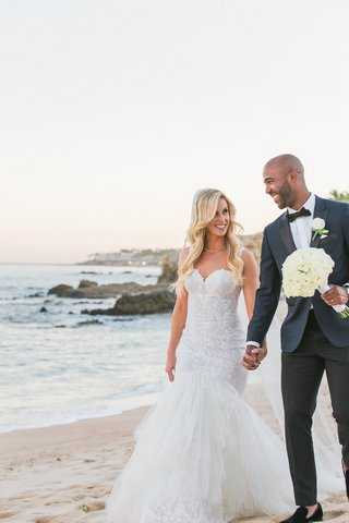 a-newlywed-couple-in-a-wedding-dress-and-blue-tuxedo-walks-on-beach-mexico