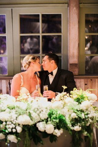 bride-in-galia-lahav-groom-in-mens-wearhouse-about-to-kiss-sweetheart-table-wedding-toasts