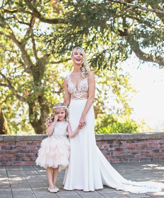 bride-in-sheer-cutout-wedding-dress-with-flower-girl-in-cute-dress-layer-ruffle-skirt-halo-headband