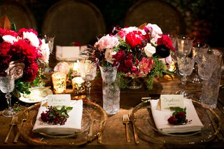 reception-with-wood-table-clear-charger-plate-gold-rim-flower-at-place-setting-crystal-goblets