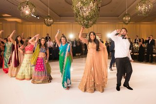 indian-wedding-bride-and-groom-doing-dance-performance-with-friends-at-reception-dance-floor