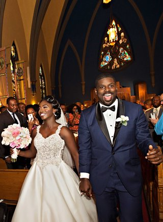bride-and-groom-in-navy-tuxedo-during-recessional-at-chicago-church-wedding-ceremony