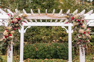 white-arch-over-altar-with-wine-colored-floral-vines-in-red-purple-pink-and-green