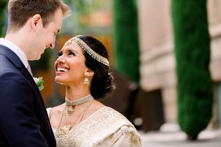 south-asian-bride-in-gold-sari-gazing-up-at-white-groom-in-suit