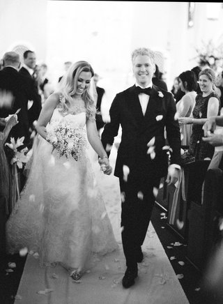 black-and-white-photo-of-bride-and-groom-leaving-church-ceremony-flower-petals-thrown-by-guests