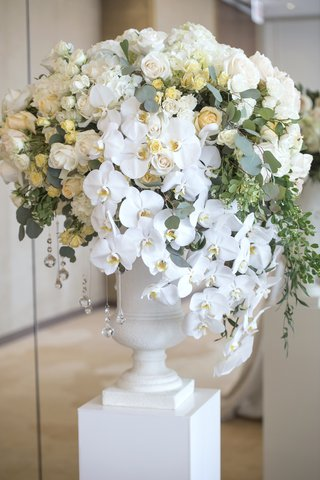 floral-arrangement-on-pedestal-with-white-orchids-small-yellow-roses-ivory-roses-eucalyptus