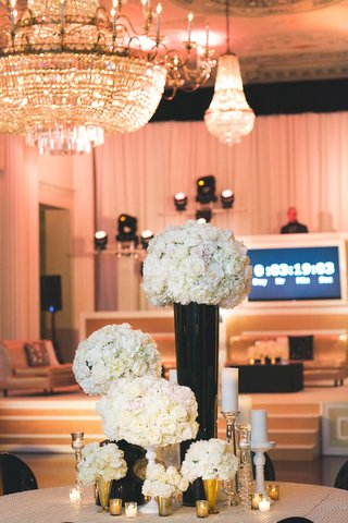 chandelier-and-countdown-next-to-round-wedding-table-with-white-rose-flowers-in-black-and-gold-vases