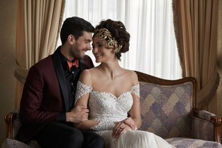 bride-in-lace-dress-and-gold-headpiece-smiling-at-groom-dark-burgundy-and-black-suit-orange-bow-tie