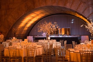 circular-tables-with-white-table-linens-with-white-floral-arrangements-of-varying-sizes