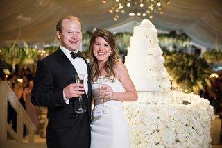 wedding-reception-tented-decor-bride-in-strapless-wedding-dress-groom-in-tuxedo-champagne-toast-cake