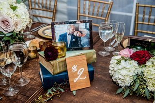wedding-table-number-held-with-books-framed-engagement-photo-on-top